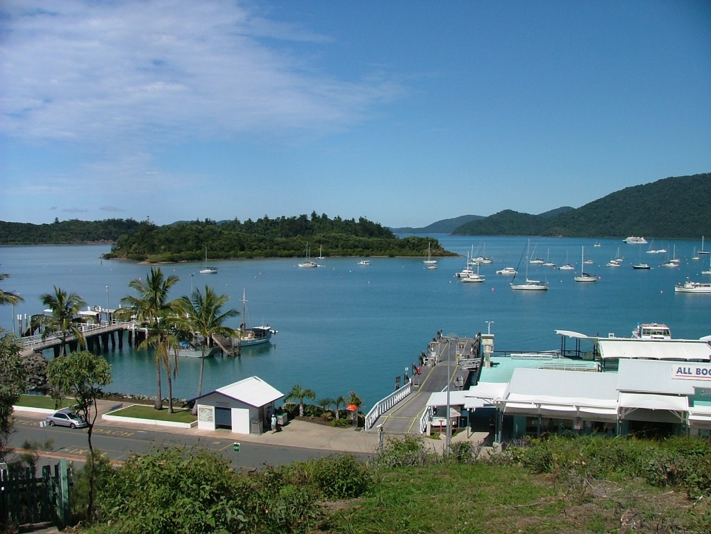 Picturesque scene overlooking building and large jetty on shore next to large tropical bay with lots of moored boats and an island.