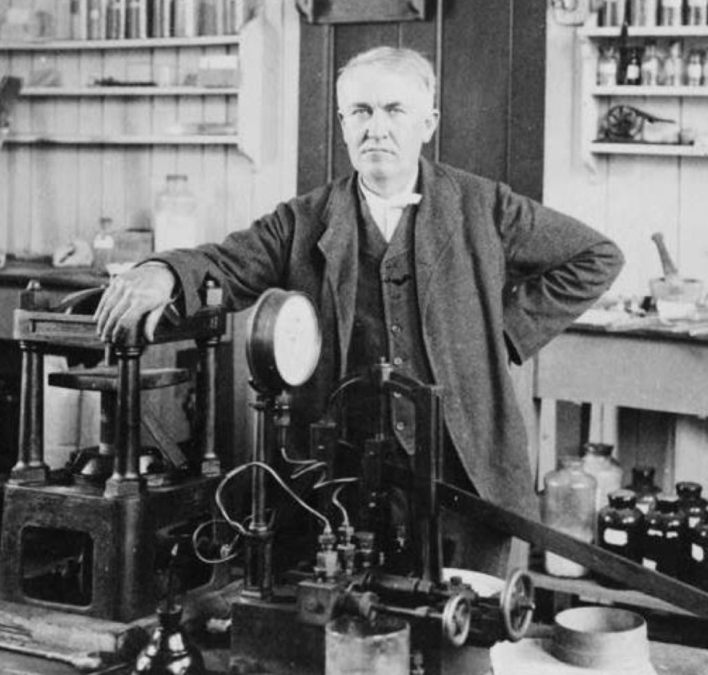 Image of Thomas Edison in his laboratory with various items of equipment.