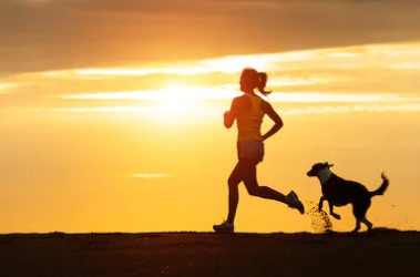 Beautiful scene of Woman running followed by dog, with setting sun behind them.