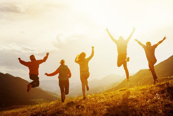 Happy image of the rear of five young people leaping into the air, with the bright sun glaring through them.