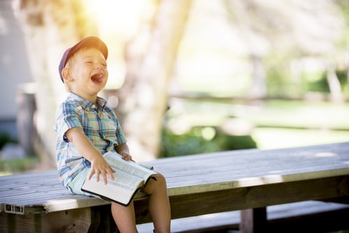 Image of young boy sitting on a park bench laughing wildly.