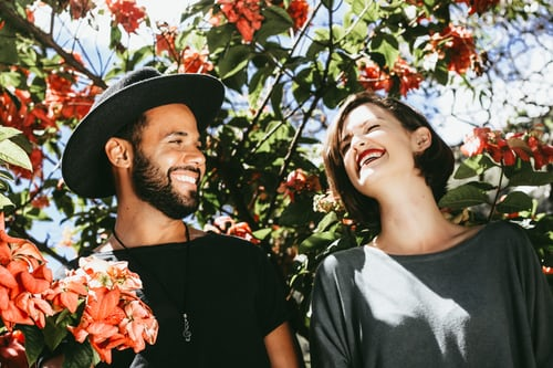 Smiling young woman and man, partially shaded by a large shrub.