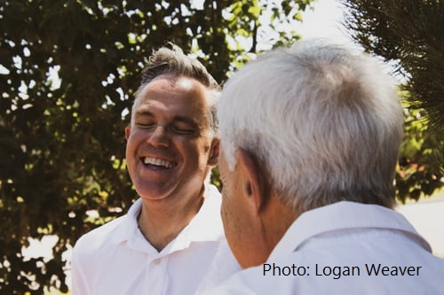 Images showing basically just the heads and shoulders of two men, one laughing with eyes closed, the other with back to camera.