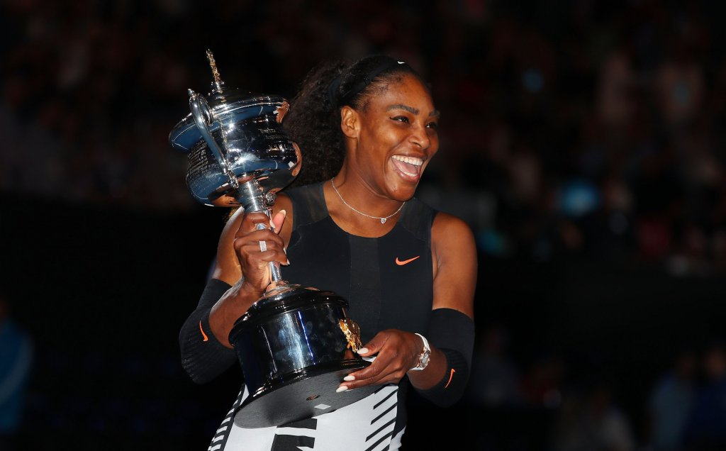 Lovely image of happy Serena Williams holding a large trophy.