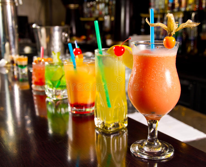Beautiful looking Tropical cocktails lined up along bar top.