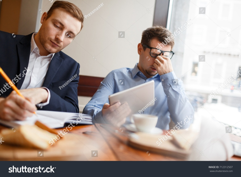 Two stressed men in an office.