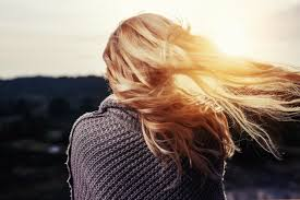 Rear view of woman with long blonde hair streaming in the wind, with setting sun slightly visible in background.