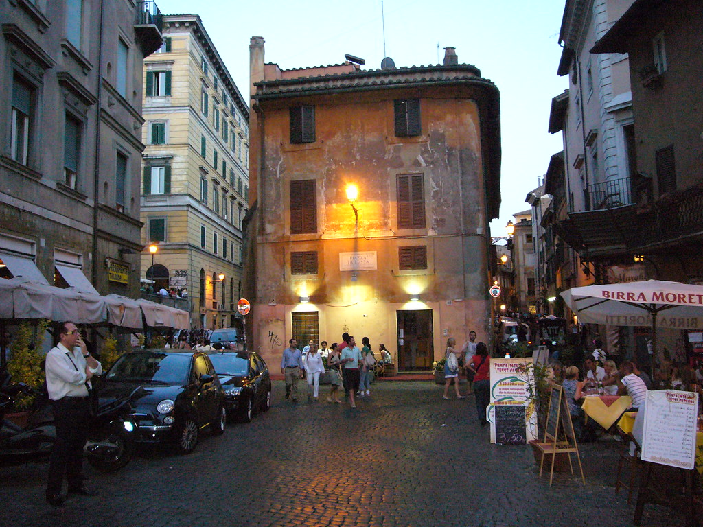 Picturesque scene of European looking cobblestone street with cafes and shops, people mingling, in the evening half light.