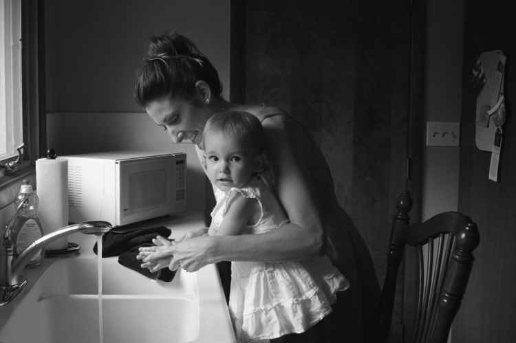 Image of Mother washing toddlers hands in sink.