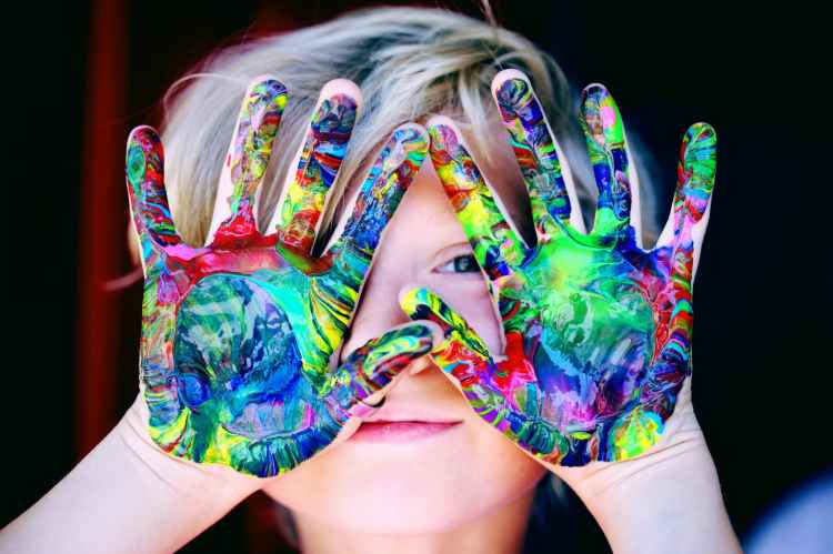 Happiness image of a child with paint all over the palms of their hands.