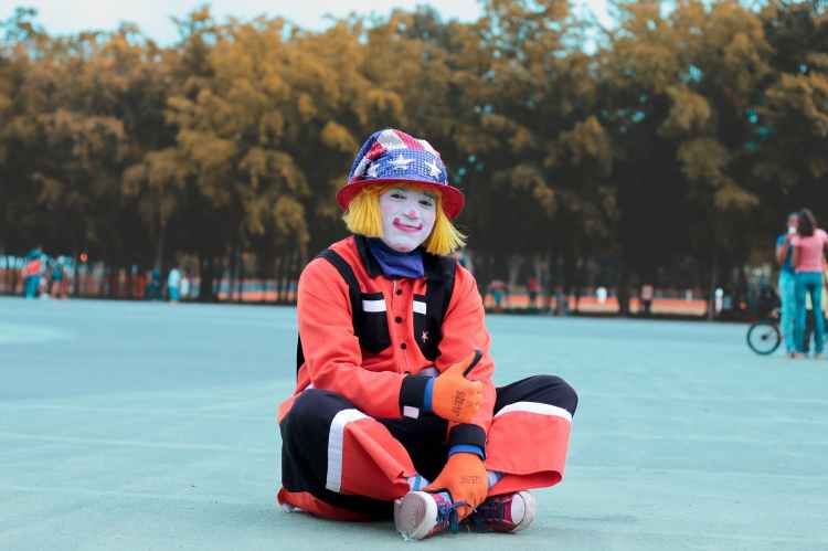 Funny joke shows a clown sitting and giving thumbs up sign.