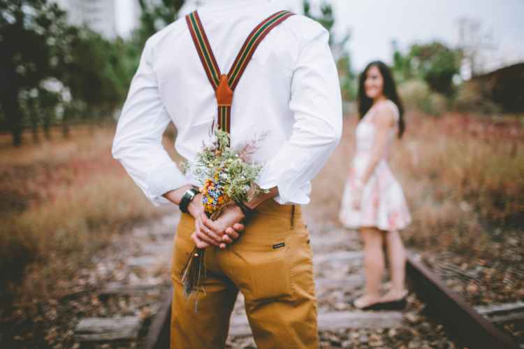 Happiness image of young man and woman.  Man has a bunch of flowers hidden, waiting to give to woman.