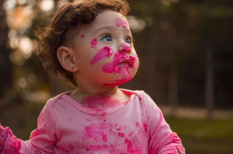 Funny image of a young child with play type paint over it's face and clothes.
