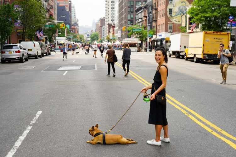 A dog on a leash with a woman owner, has stopped and lain on it's stomach in the middle of a street.