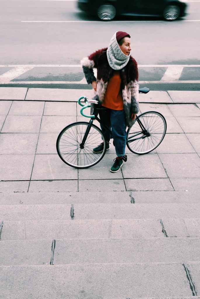 Woman with bicycle on sidewalk.