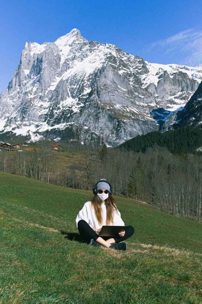 Photo of scene of green meadow and snow capped mountains in background, with young lady sitting on the grass with a laptop on lap and wearing health safety mask.