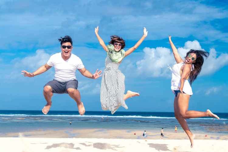 Happiness image of three young people jumping in the air at a beach.