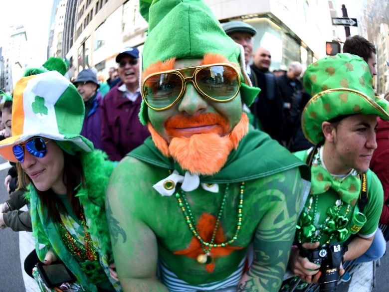 Three people with complete gree outfits and gear at a St Patrick's Day parade.