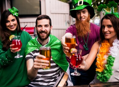 Four people in some green clothes celebrating St Patrick's Day.