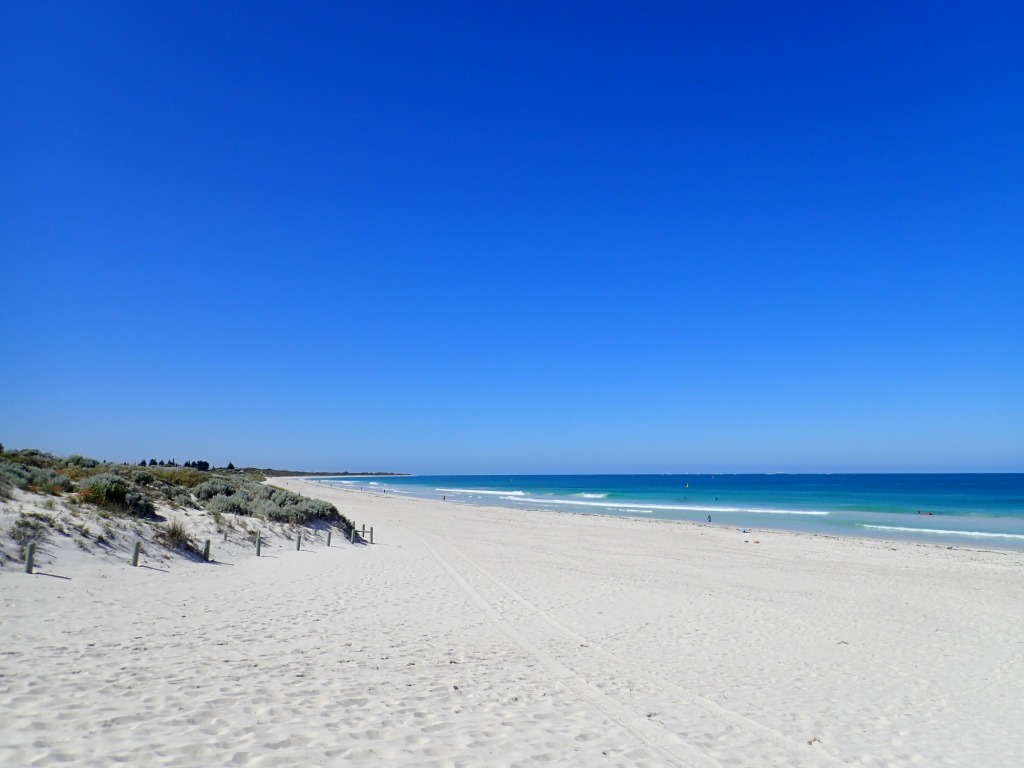 Beautiful Beach with white sand and small waves lapping the edge.  Water has many shades of blue.  Sky is clear and a beautiful shade of blue.
